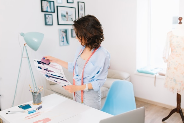 Brunetka dziewczyna w szarej sukience i niebieskiej koszuli stoi przy stole w pracowni warsztatowej. patrzy na próbki materiałów i szkice w dłoniach.