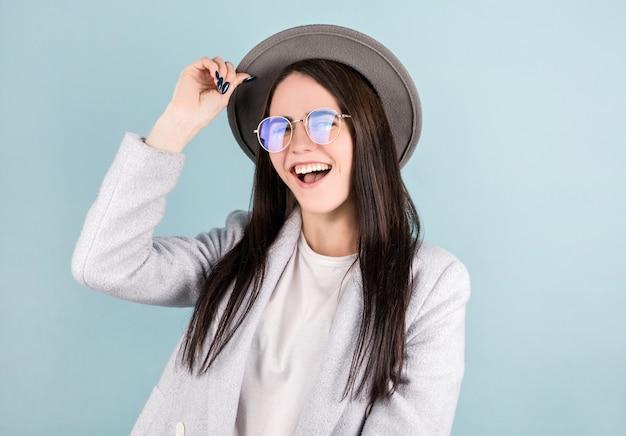 Brunetka dziewczyna w szarym kapeluszu w białej koszulce tańczy z natchnionym wyrazem twarzy.