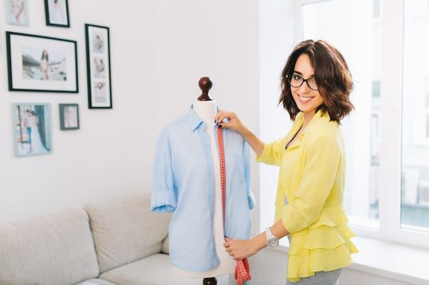 Brunetka dziewczyna w żółtej kurtce robi dopasowaną koszulę na manekinie. pracuje w dużej pracowni warsztatowej. ona uśmiecha się do kamery.