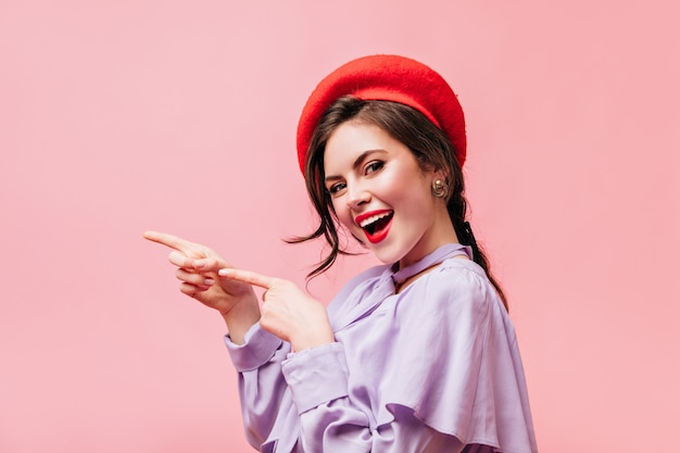 Brunetka dziewczyna z czerwoną szminką uśmiecha się i wskazuje palcami w lewo. portret kobiety w berecie z miejscem na tekst na różowym tle.