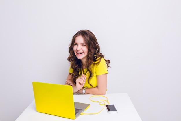 Brunetka dziewczyna z kręconymi włosami śmieje się przed laptopem w żółtej obudowie.