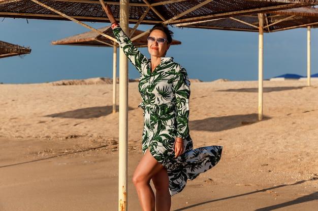 Brunetka dziewczyna z krótkimi włosami w sukience pozowanie na plaży w pobliżu parasola od słońca. dziewczyna w sukience pozuje na plaży
