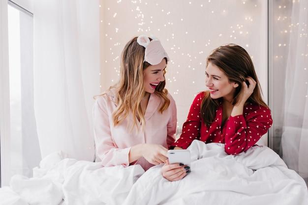 Brunetka dziewczyna z nieśmiałym uśmiechem pokazuje telefon siostrze podczas chłodzenia w łóżku. kryty portret przyjemnych koleżanek relaks w weekendowy poranek.