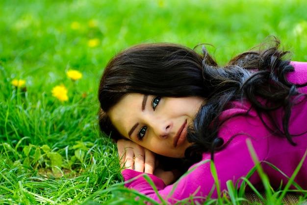 Brunetka dziewczynka czerpie przyjemność na trawie z mniszka lekarskiego, portret na zewnątrz. zamknij twarz