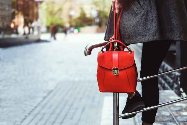 Brunetka dziewczynka siedzi na barierę z czerwonym plecakiem