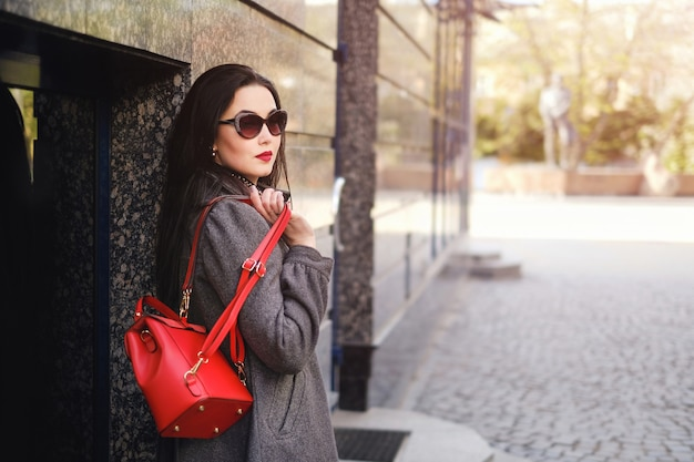 Brunetka dziewczynka spaceru na ulicy z czerwonym plecakiem