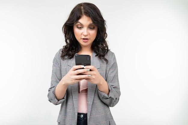 Brunetka dziewczynka surfuje po internecie trzymając w rękach telefon