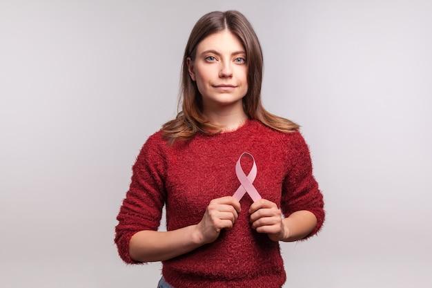Brunetka dziewczynka trzymająca różową wstążkę, symbol świadomości raka piersi, patrząc na kamerę