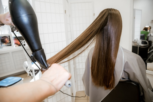 Brunetka dziewczynka w salonie piękności, pielęgnacja włosów. strzyżenie, farbowanie i mycie włosów u fryzjera.