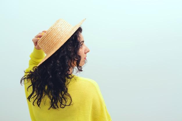 Brunetka dziewczynka z długimi kręconymi włosami. ładna kobieta nosi kapelusz i żółty sweter.