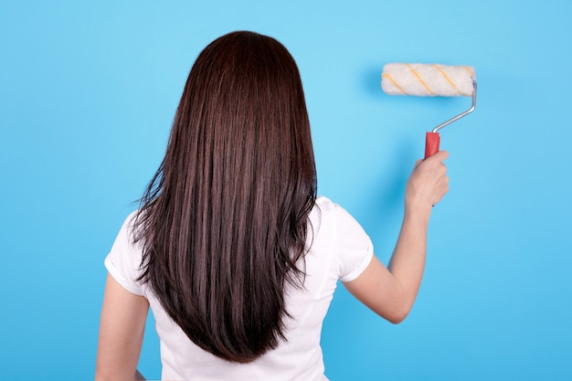 Brunetka dziewczynka z długimi włosami za pomocą wałka do malowania, widok z tyłu. pojedynczo na niebieskim tle.