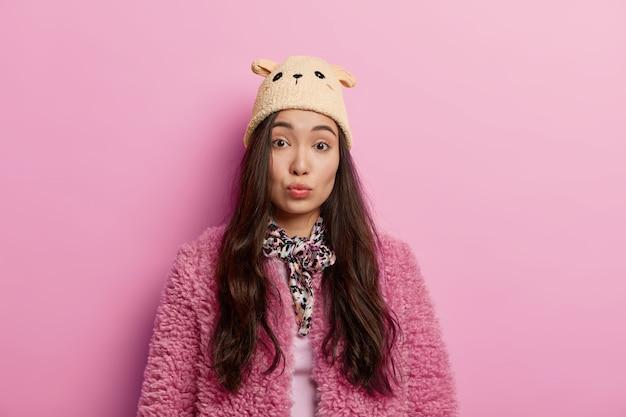 Brunetka etniczna dziewczyna wygląda ze spokojnym melancholijnym wyglądem, ma złożone usta, słucha czegoś, nosi kapelusz i różowy płaszcz