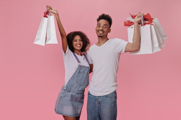 Brunetka facet i dziewczyna szczęśliwie pozują z torbami na zakupy na różowej ścianie