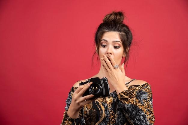 Brunetka fotograficzna dziewczyna sprawdza swoje zdjęcia w aparacie i wygląda na niezadowoloną.