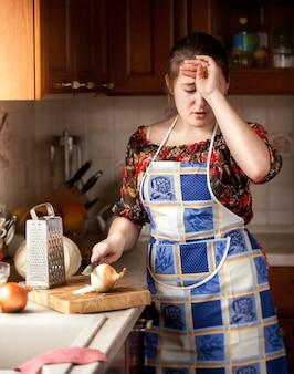Brunetka gospodyni domowa płacze podczas krojenia cebuli