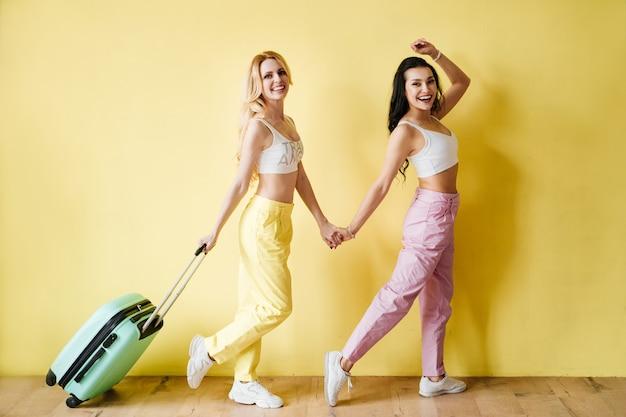 Brunetka i blondynka w kolorowe spodnie na żółtej ścianie. kolor różowy i żółty. podróżowanie z miętową walizką i ananasem.