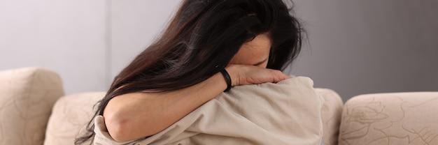 Brunetka kobieta chowa głowę w poduszce. pomoc z koncepcją depresji