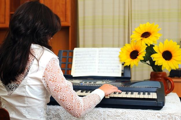 Brunetka kobieta gra muzykę na pianinie w domu. uwaga, wazon ze słonecznikami na stole. wnętrze domu na tle. widok z tyłu
