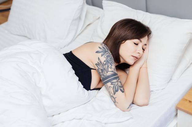Brunetka kobieta leży na łóżku rano obudzić, rozciągając ręce i ciało