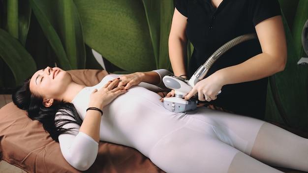 Brunetka kobieta leży w centrum medycyny po sesji leczenia lpg ze specjalnym aparatem