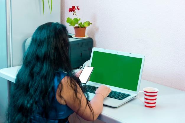 Brunetka kobieta odwrócona plecami do aparatu robi zakupy w internecie, płacąc kartą bankową online green screen. zdjęcie poziome