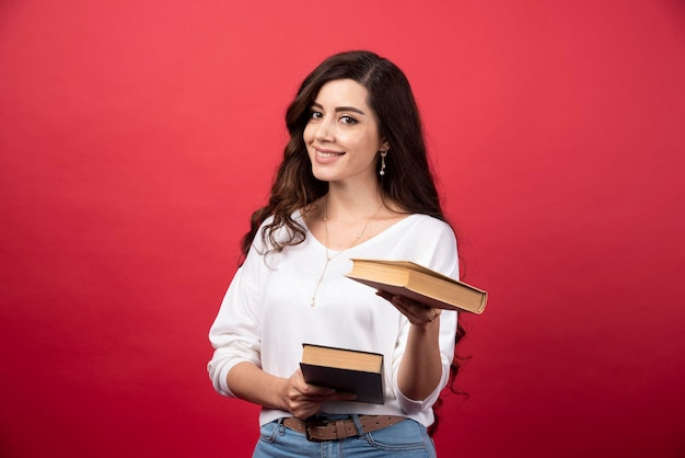 Brunetka kobieta oferuje książkę na czerwonym tle. zdjęcie wysokiej jakości