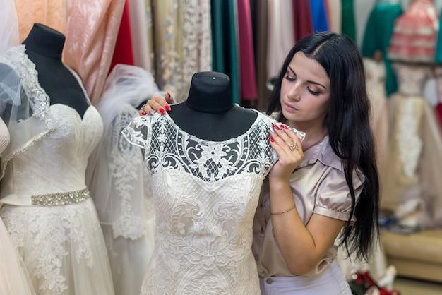 Brunetka kobieta patrząc na suknię ślubną w salonie