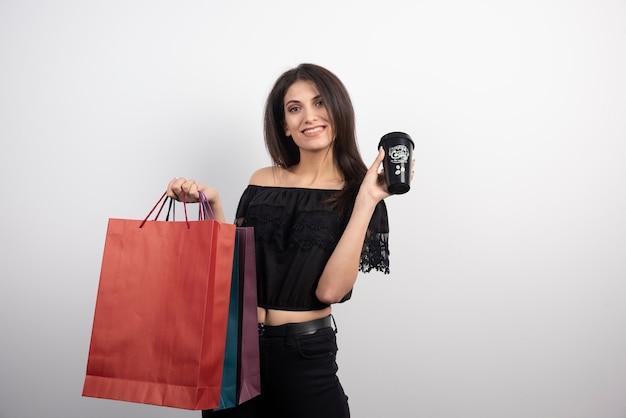 Brunetka kobieta pokazuje filiżankę kawy
