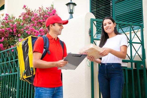 Brunetka kobieta przyjmując paczkę od profesjonalnego doręczyciela. szczęśliwy listonosz dostarczający zamówienie do klienta, stojący na zewnątrz i uśmiechnięty. dostawa do domu i koncepcja poczty