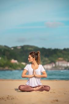 Brunetka kobieta samotnie praktykuje jogę na plaży. ubrana w białą koszulkę. ona jest boso. ona jest przeciw błękitnemu niebu