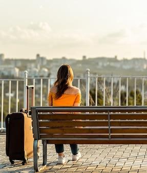 Brunetka kobieta siedzi na ławce w parku i patrząc w horyzont z walizką w pobliżu.
