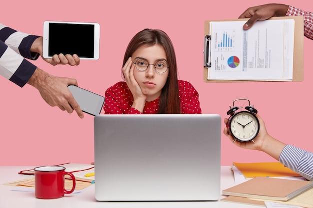 Brunetka kobieta siedzi przy biurku, otoczona gadżetami i papierami