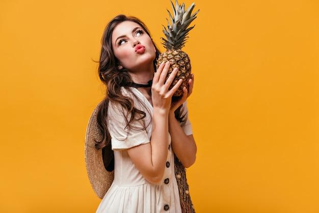 Brunetka kobieta skrzywi się i trzyma ananas na pomarańczowym tle.