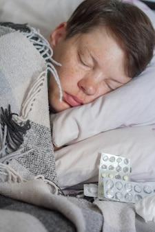 Brunetka kobieta śpi w łóżku pod kocem w kratę z pigułkami
