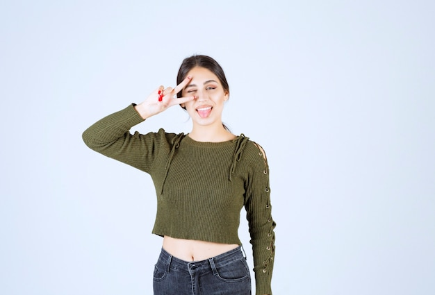 Brunetka kobieta stojąc i pokazując szczęśliwą twarz do kamery.