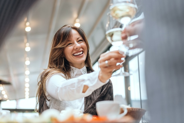 Brunetka kobieta szczęk szklanki z przyjacielem w kawiarni.