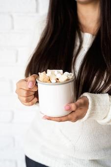 Brunetka kobieta trzyma kubek kakao ptasie mleczko