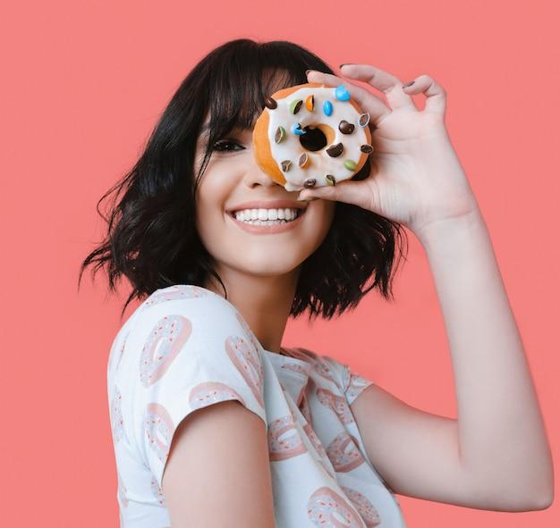 Brunetka kobieta trzyma smaczny pączek uśmiechając się do kamery na różowej ścianie studio