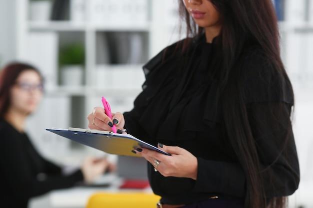 Brunetka kobieta trzyma w ramionach różowy długopis i papier przycięty do podkładki zbliżenie kolegów