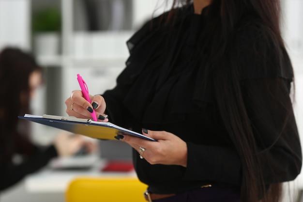 Brunetka kobieta trzyma w ramionach różowy długopis i papier