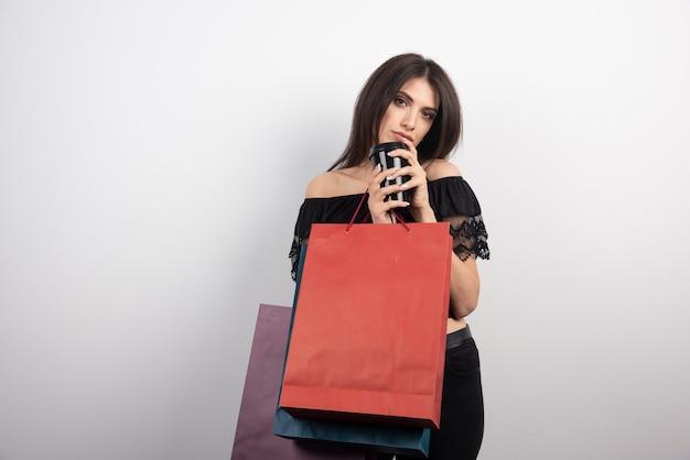 Brunetka kobieta trzymając torby na zakupy i filiżankę kawy.