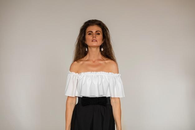 Brunetka kobieta ubrana w białą bluzkę i czarną spódnicę