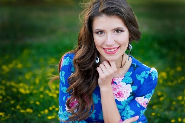 Brunetka kobieta uśmiecha się na letniej zielonej polanie z kwiatami