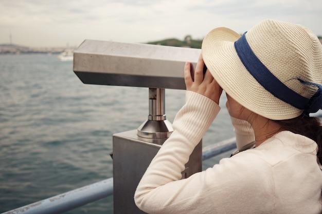Brunetka kobieta w białym swetrze i kapeluszu patrzy przez lornetkę badając zbliżenie pejzażu miejskiego