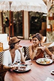 Brunetka kobieta w brązowej czapce i białej koszulce i jej przyjaciółka w stylowej górze uśmiecha się i odpoczywa w ulicznej kawiarni