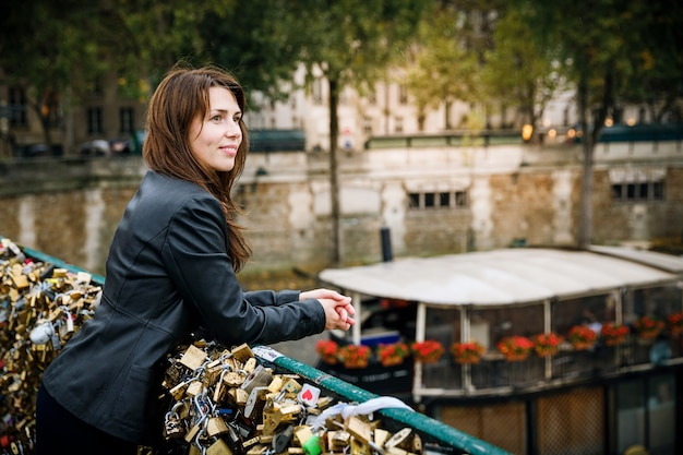 Brunetka kobieta w czarnej kurtce stoi na moście