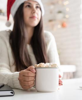 Brunetka kobieta w santa hat trzyma kubek kakao ptasie mleczko