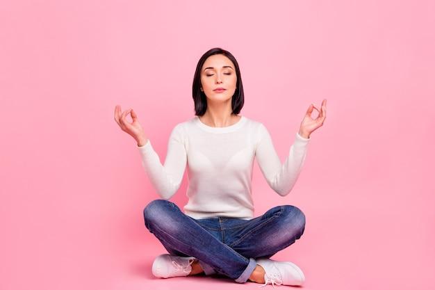 Brunetka kobieta z białym swetrem siedzi na podłodze na różowym tle