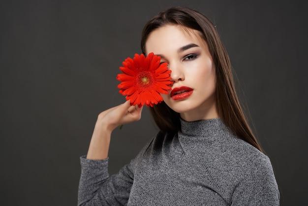 Brunetka kobieta z czerwonym kwiatem jasny makijaż kosmetyki ciemne tło