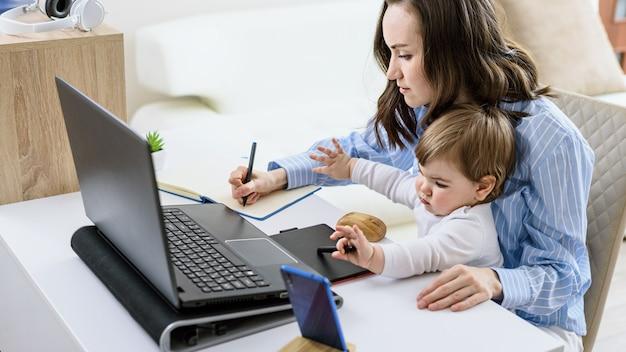 Brunetka kobieta z dzieckiem siedzi przy laptopie, robiąc notatki w notatniku